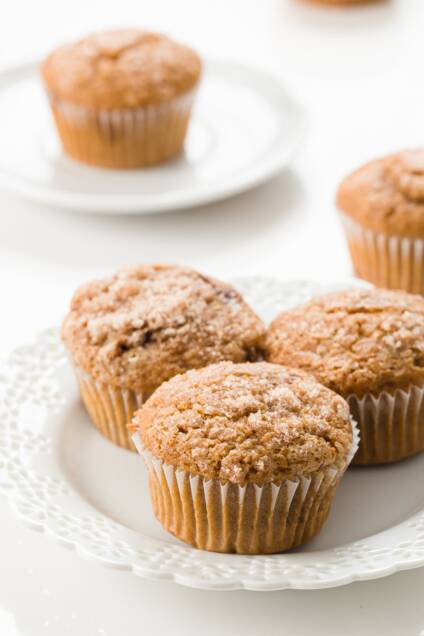 Three cinnamon muffins on a white plate with a muffin in the background