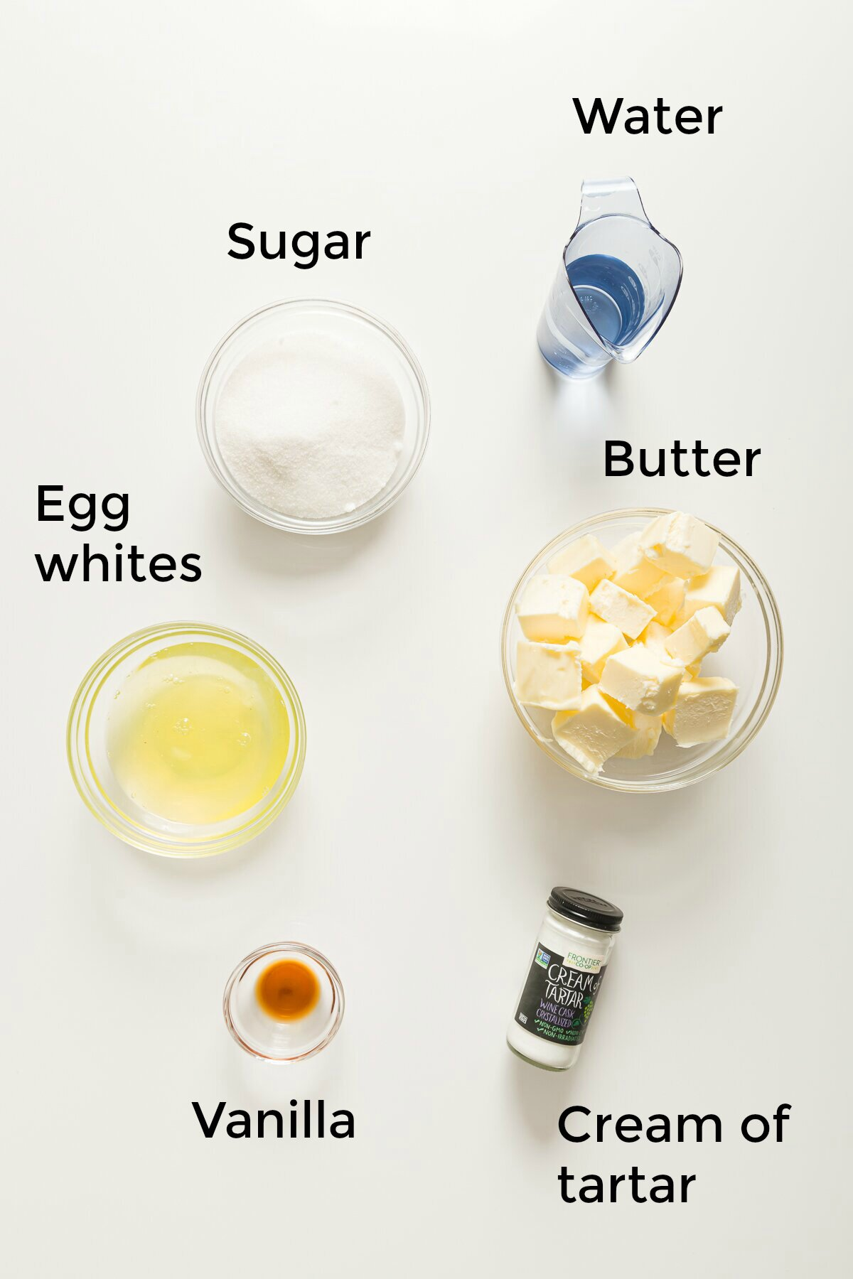 top-down view of ingredients needed to make Italian meringue buttercream frosting: sugar, water, egg whites, butter, vanilla extract, and cream of tartar