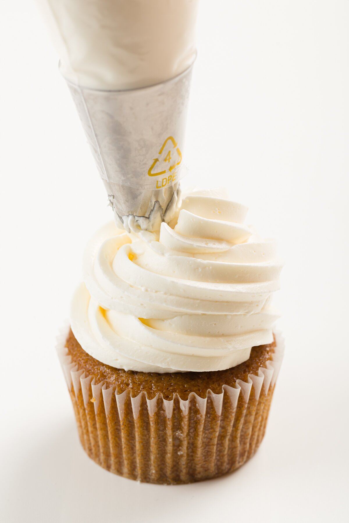 Italian meringue buttercream frosting being piped onto a cupcake