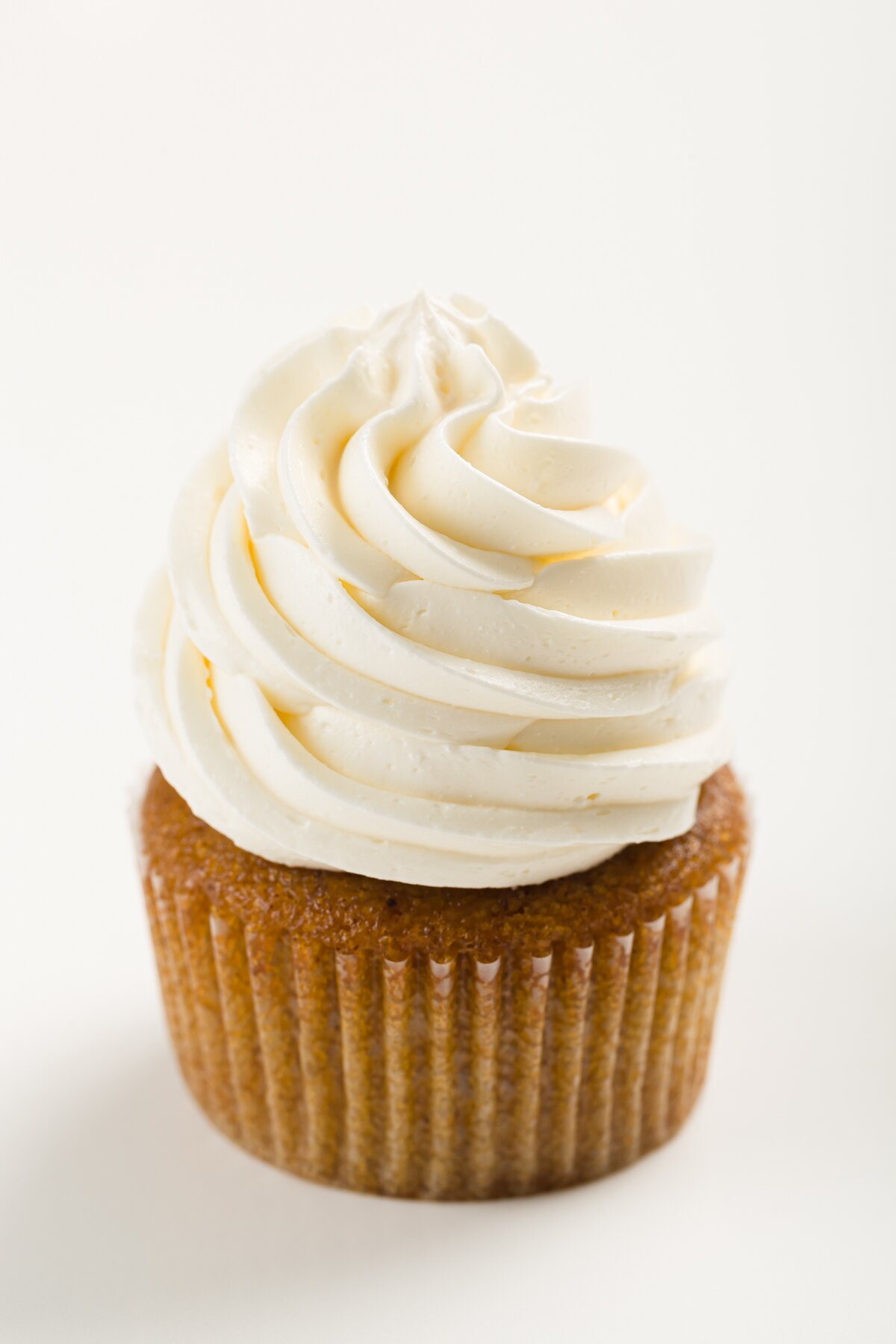 tight shot of a cupcake frosted with Italian meringue buttercream frosting
