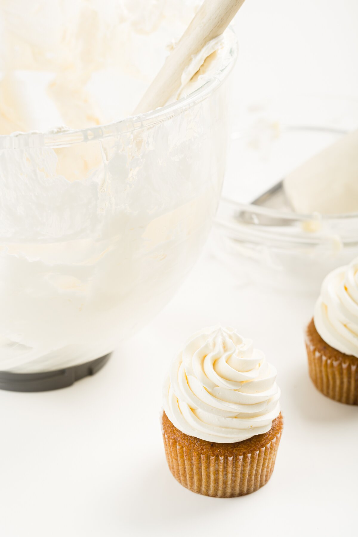 a cupcake frosted with Italian meringue buttercream frosting with a bowl of frosting behind it