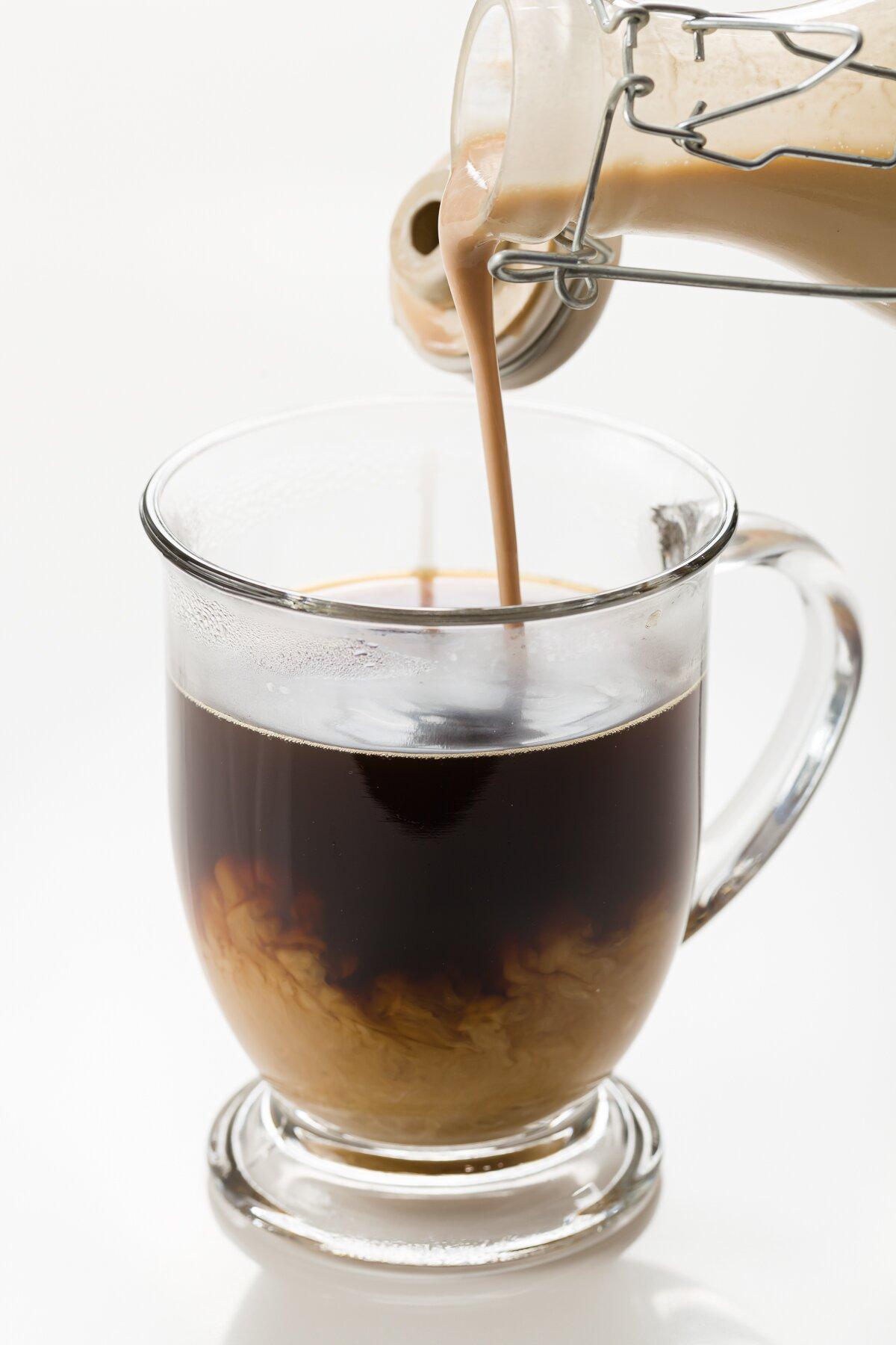 Disparo ajustado de Baileys caseros se vierte en café caliente
