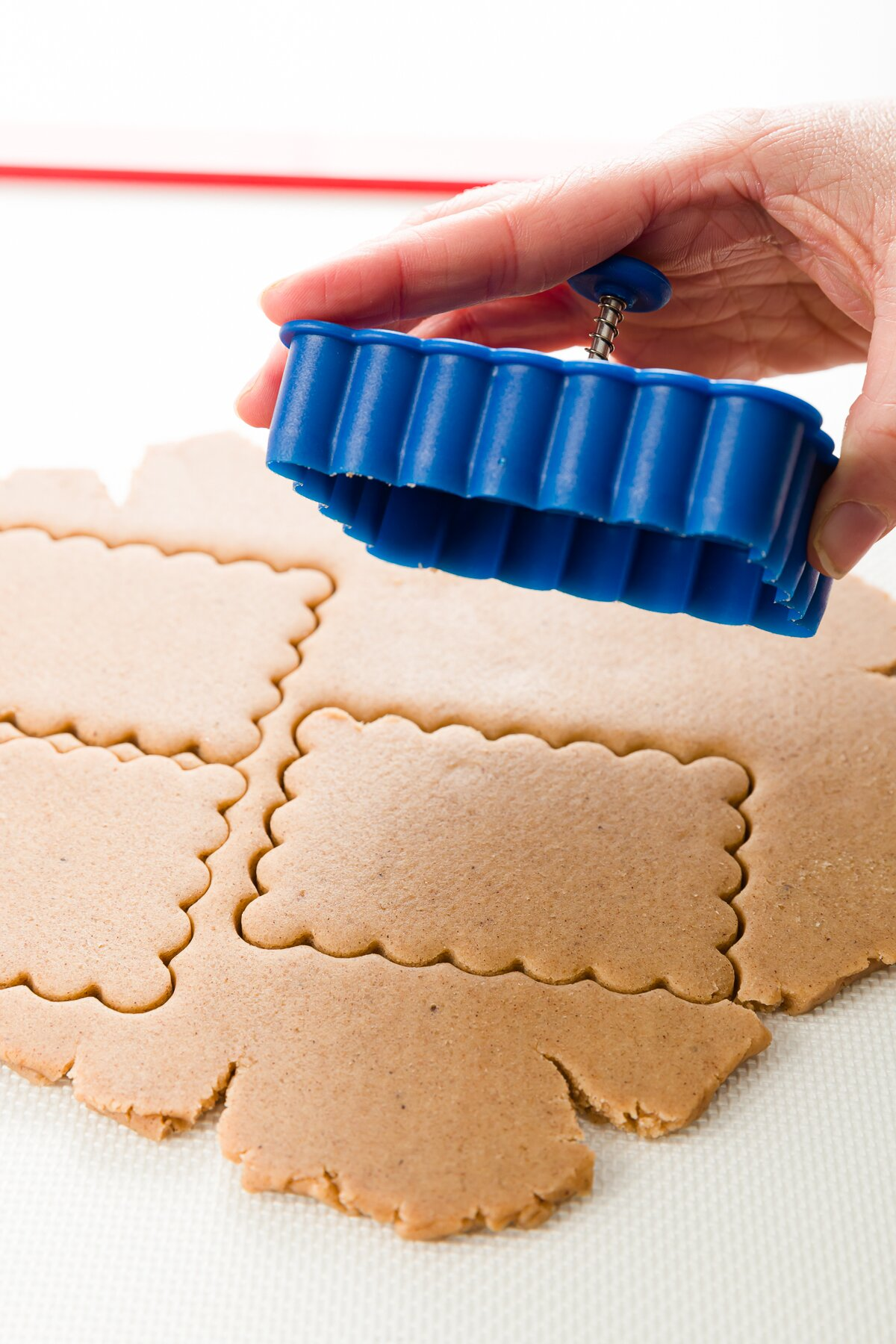 a sheet of cookie dough just cut with a scalloped rectangular cookie cutter
