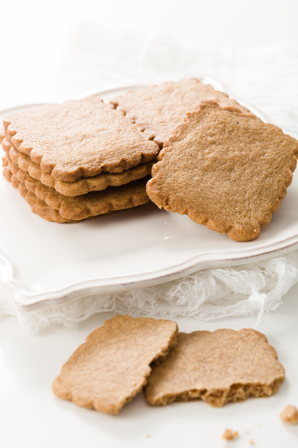 a pile of speculoos cookies on a white plate