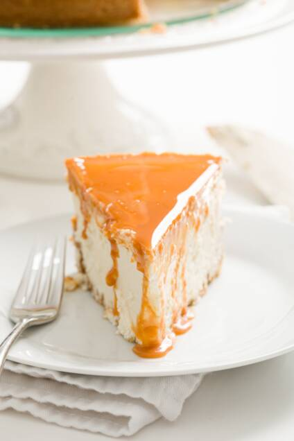 slice of cheesecake with dulce de leche dripping down it