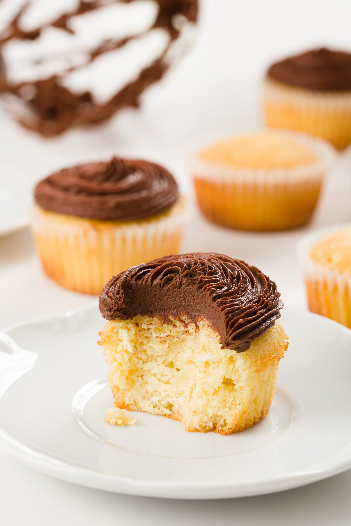 view of an interior of a pound cake cupcake frosted with chocolate ganache frosting with other cupcakes in the background