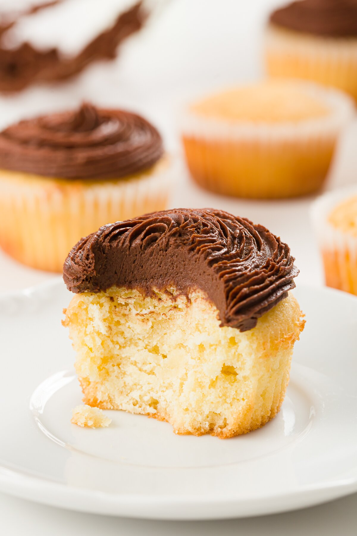 tight shot of an interior of a pound cake cupcake frosted with chocolate ganache frosting with other cupcakes in the background