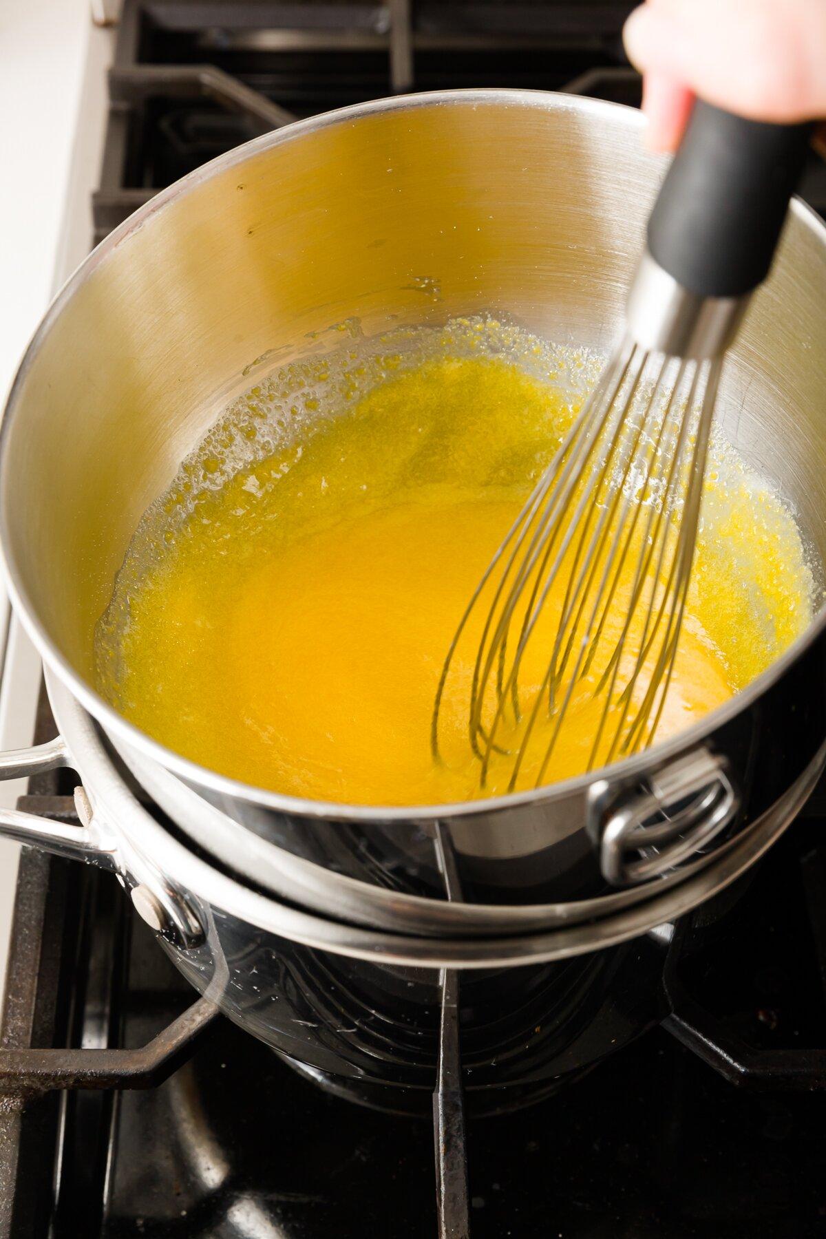 Stef batiendo las yemas de huevo y el azúcar en un bol a baño maría