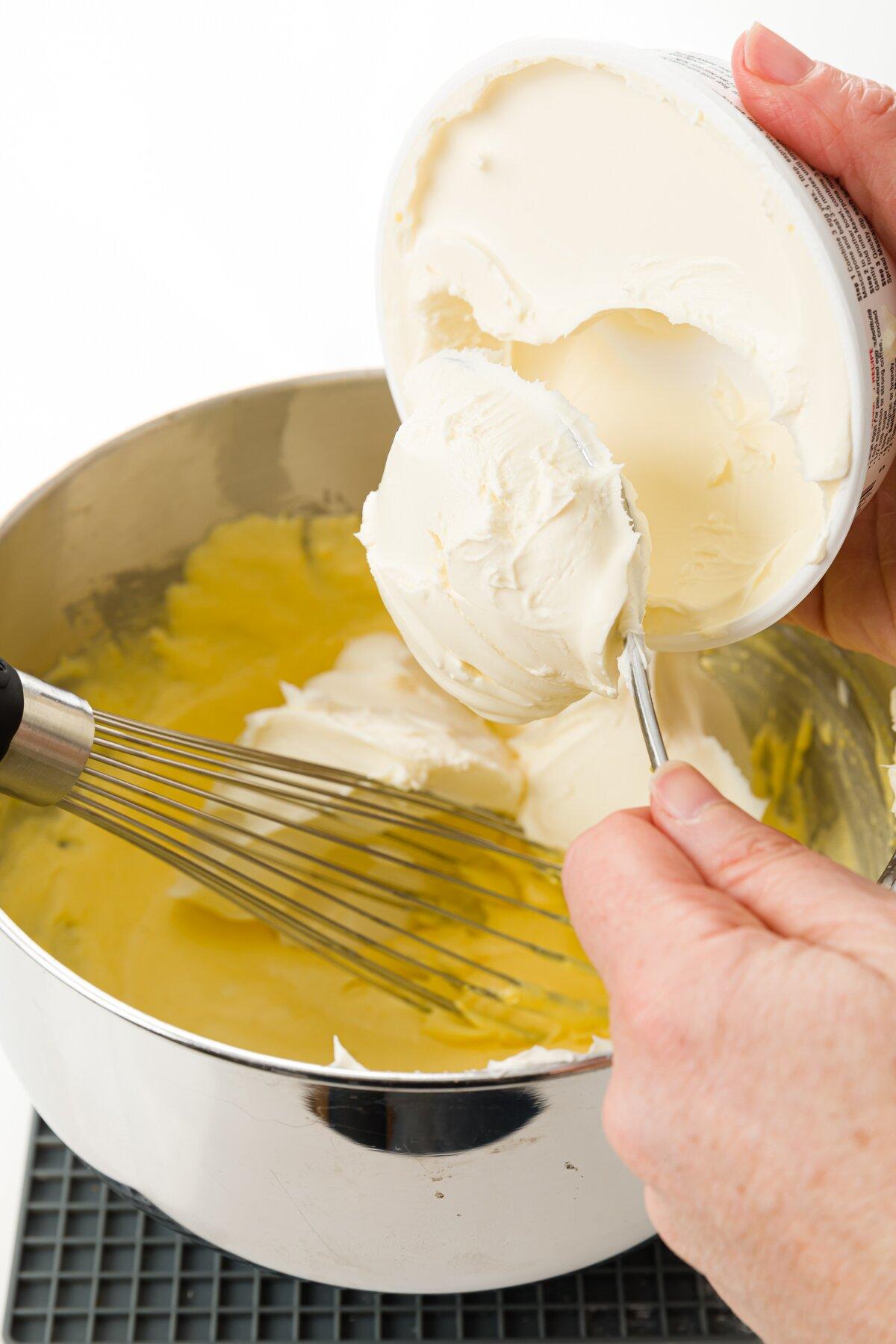 Stef agregando mascarpone a la mezcla de azúcar y claras de huevo