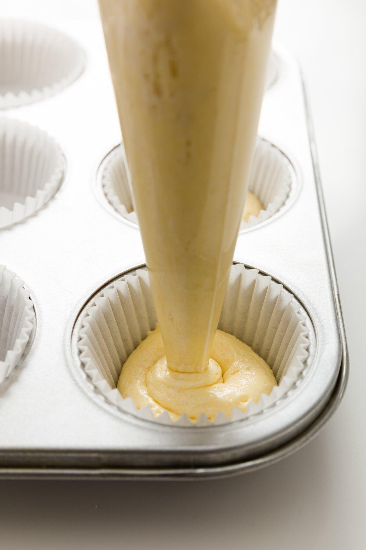 tiro ajustado de Stef canalizando la masa de cupcake tiramisú en revestimientos para cupcakes