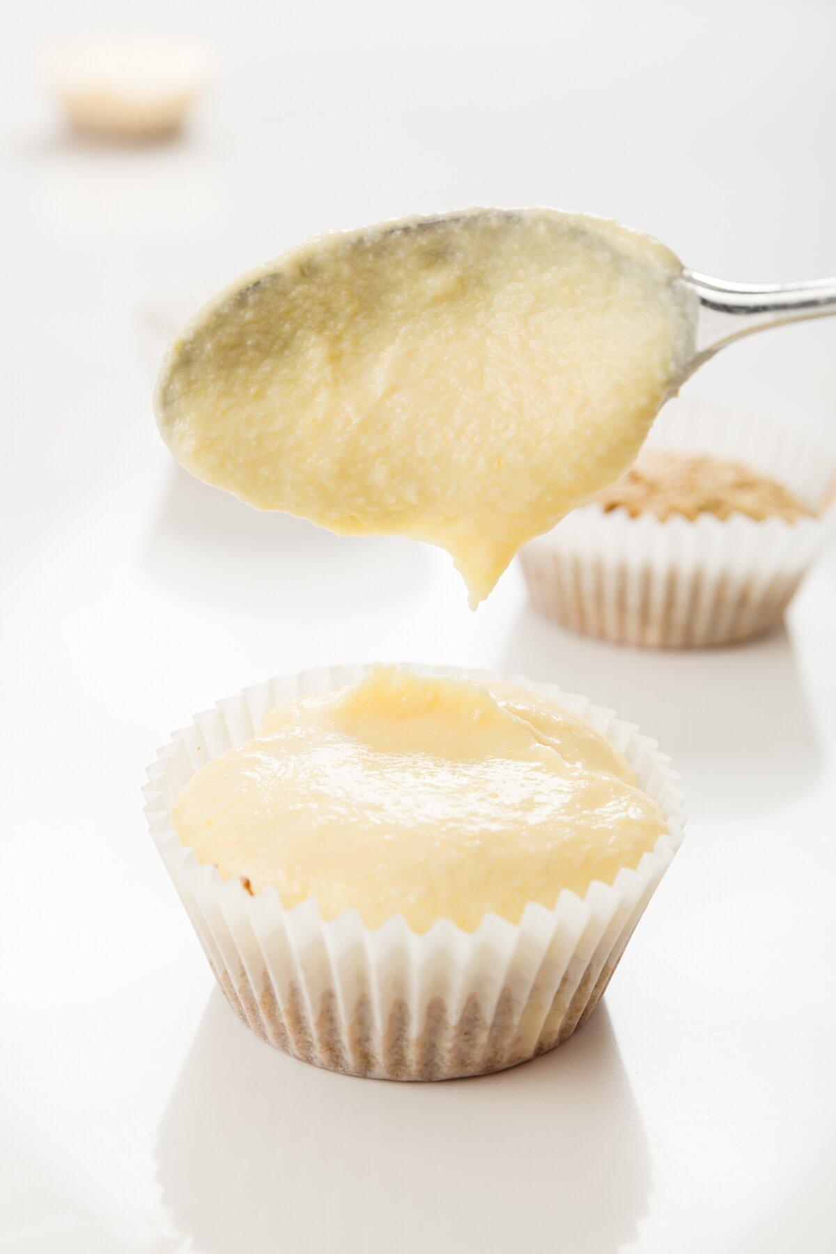 Tiro ajustado de Stef poniendo la mezcla de natillas encima de un cupcake de tiramisú