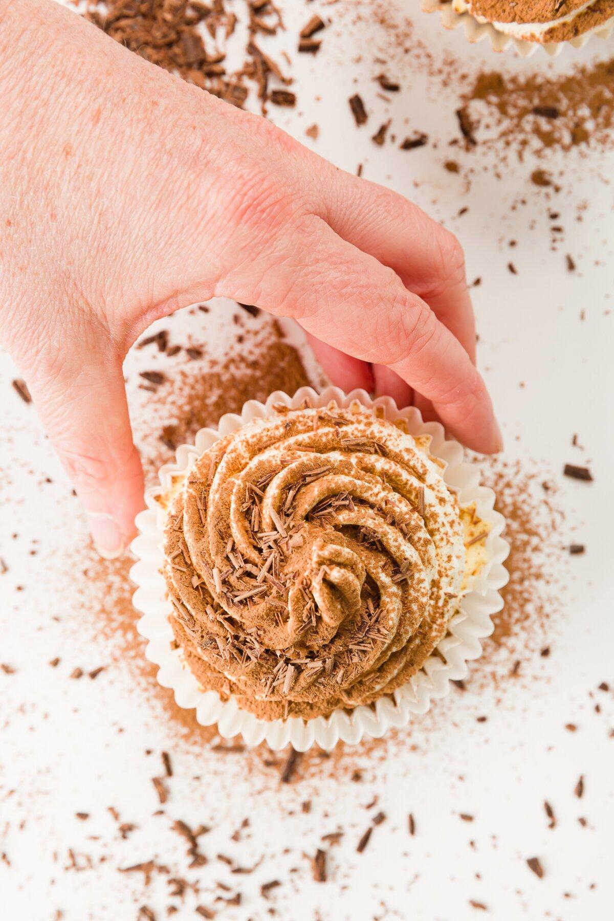 Fotografía cenital de la mano de Stef para alcanzar un cupcake de tiramisú
