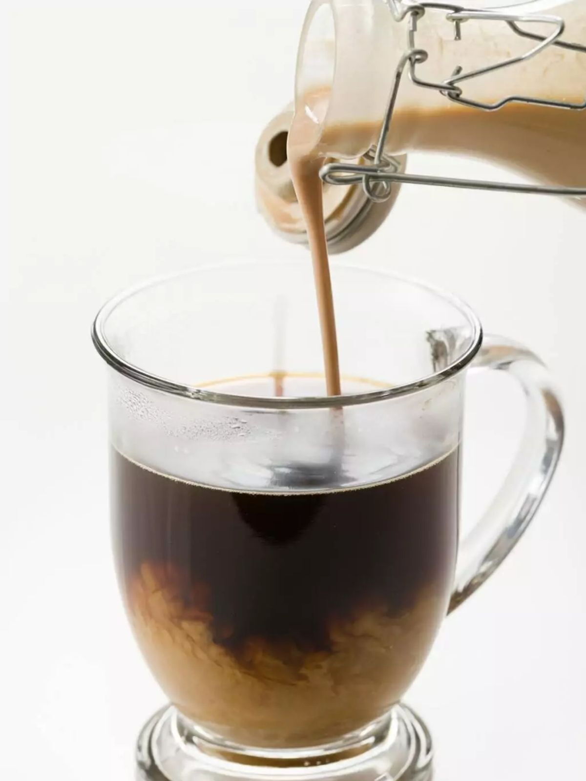 Homemade bailey's irish cream poured into a cup of coffee.