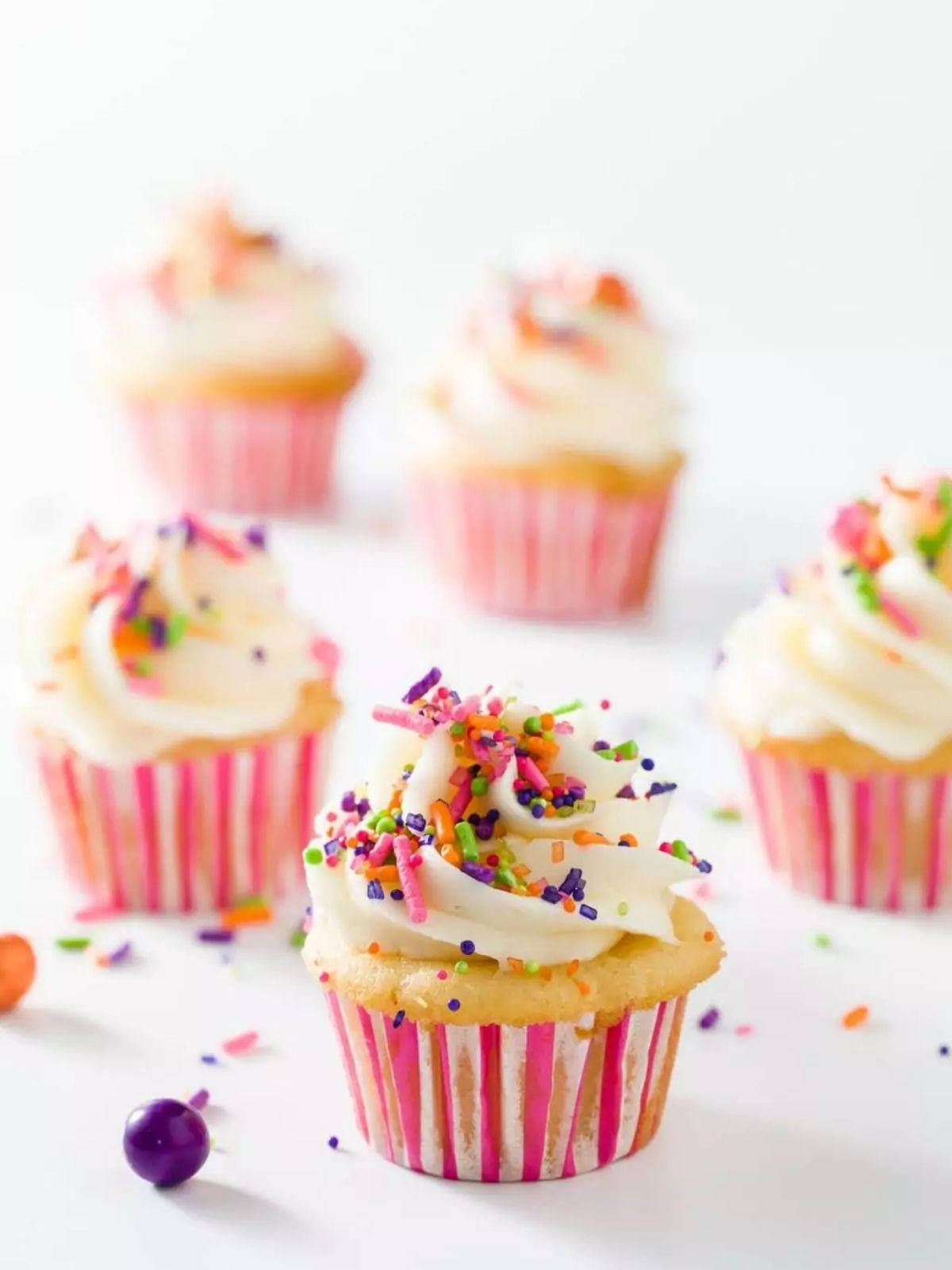 Mini cupcakes frosted with vanilla buttercream with rainbow sprinkles on top.