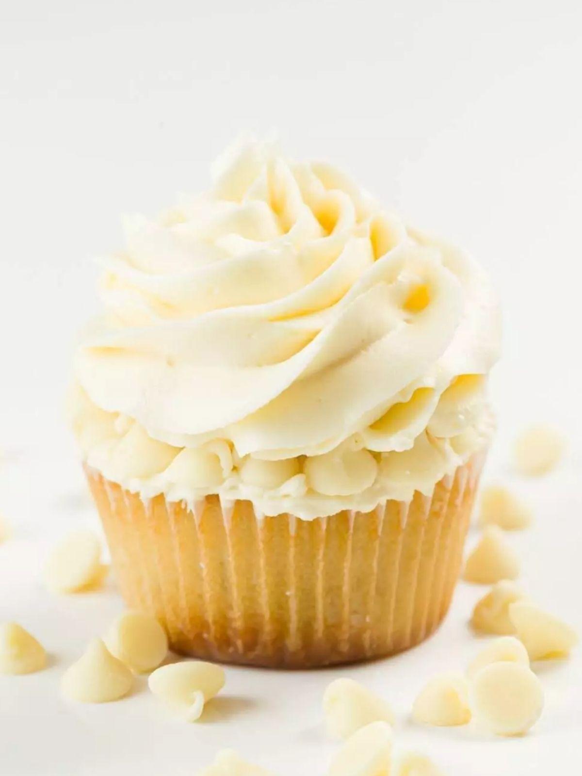 White chocolate cupcake swirled with frosting and with white chocolate chips around it.