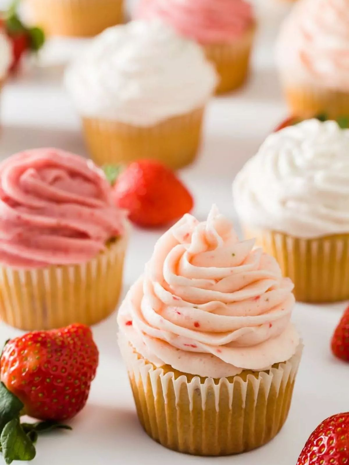 Strawberry cupcakes with strawberry buttercream frosting and fresh strawberries around them.
