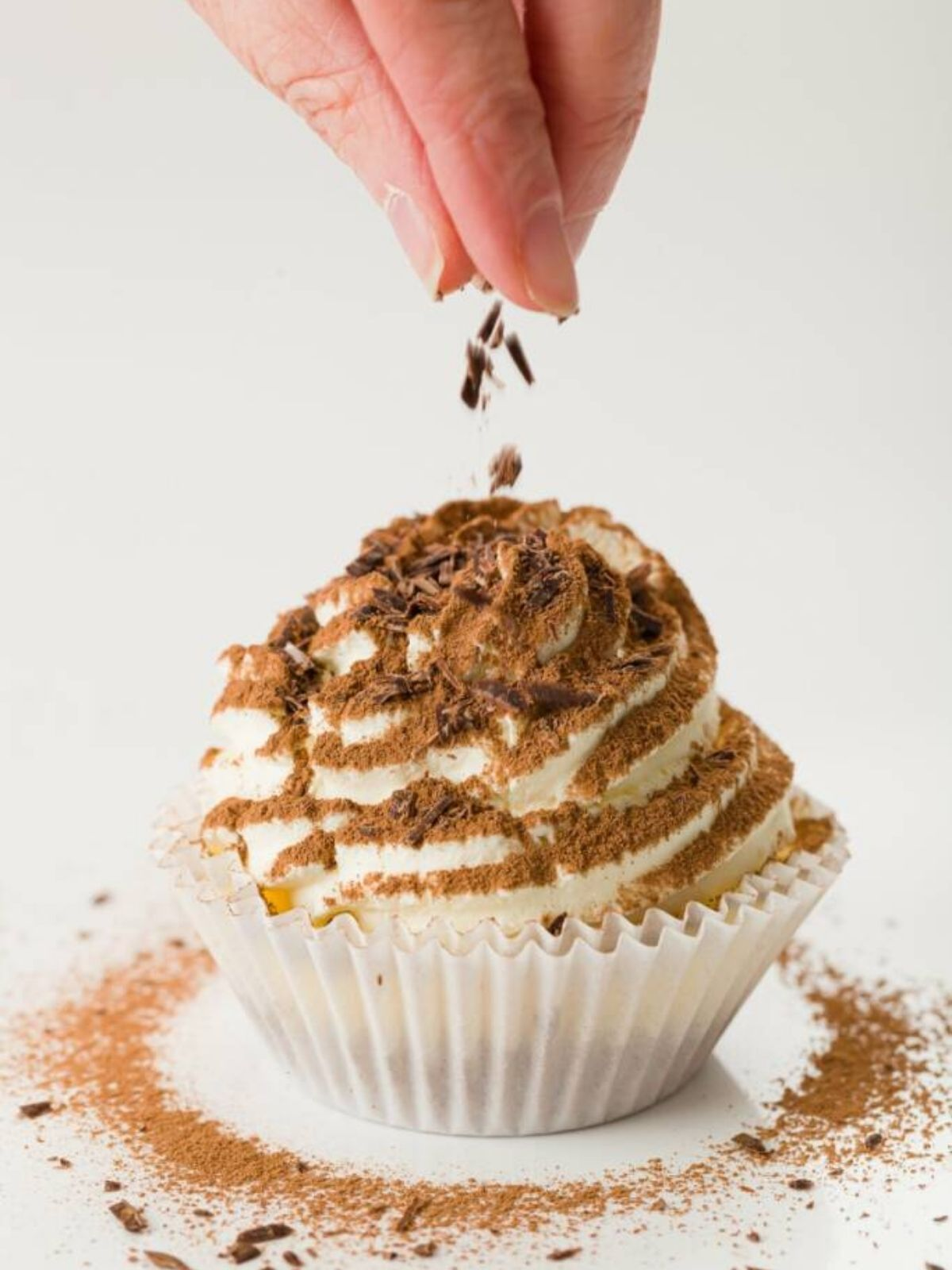 A tiramisu cupcake being topped with chocolate shavings with a halo of cocoa powder around the bottom..