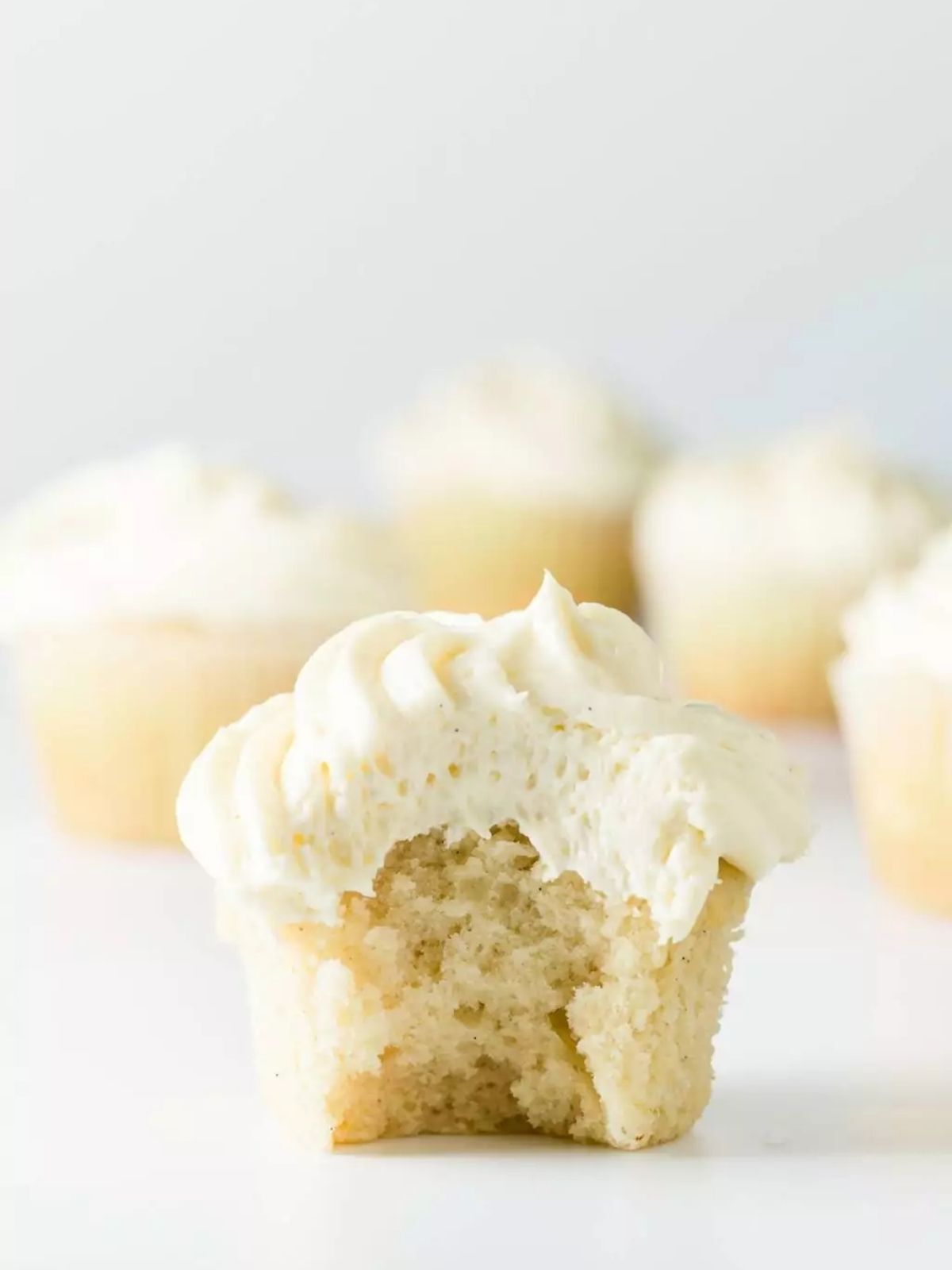 Vanilla cupcakes with a bite taken out.