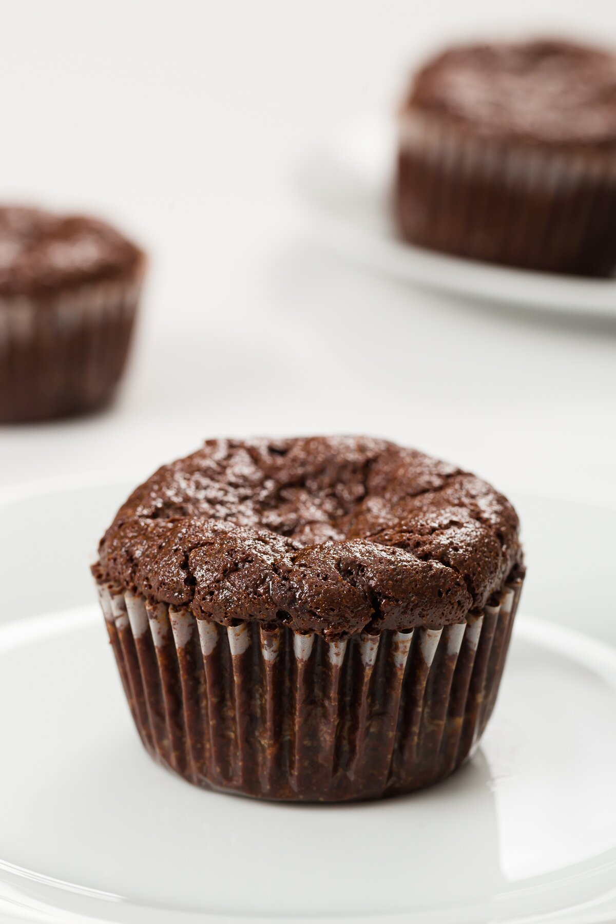 flourless chocolate cupcake on a plate with no topping and other cupcakes in the background
