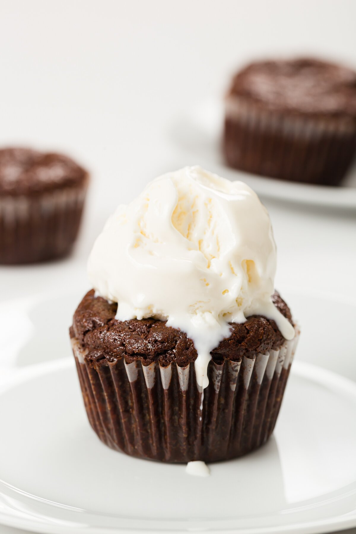 flourless chocolate cupcake with melty vanilla ice cream cream on top and some cupcakes in the background