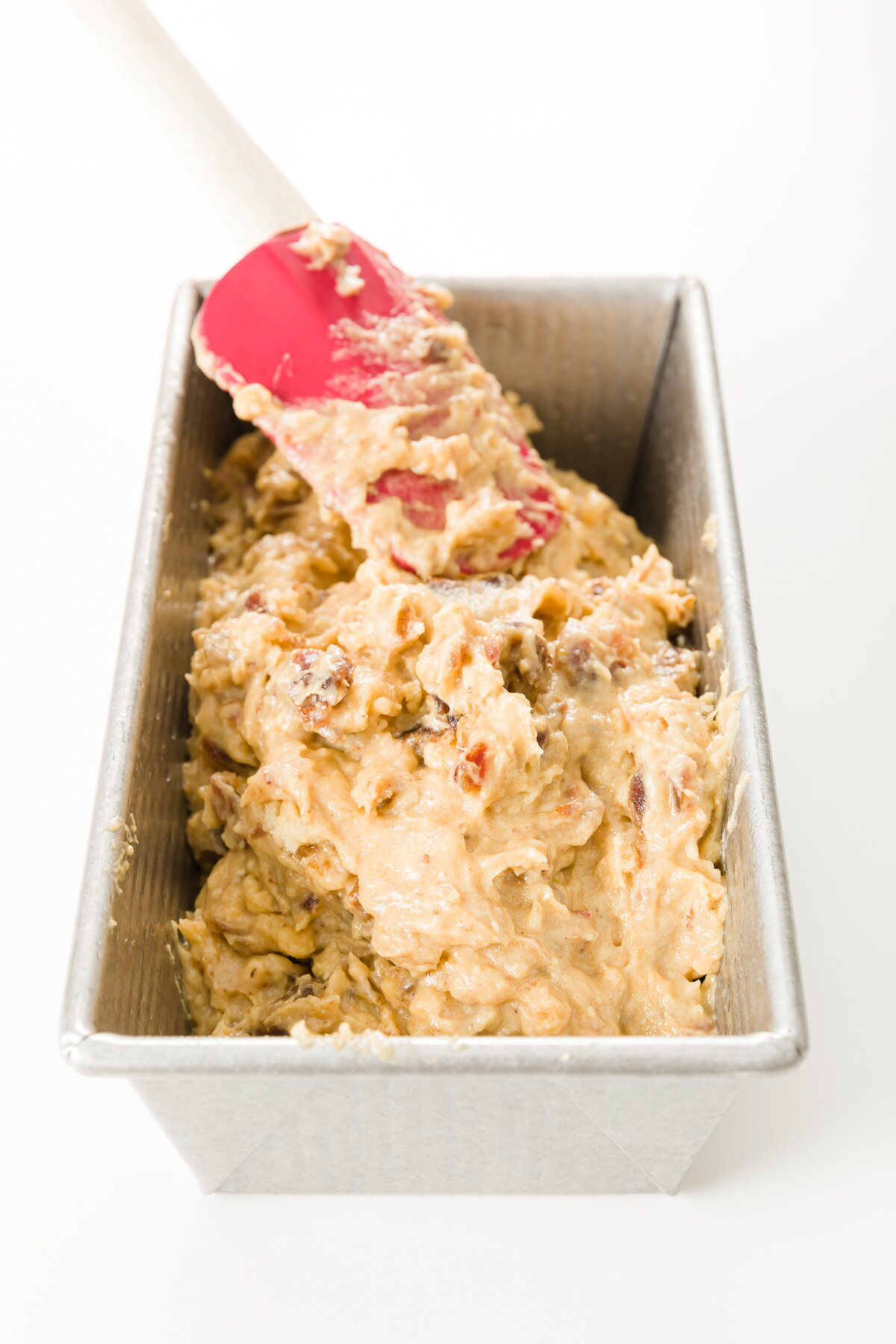 Spreading batter in a loaf pan with a red spatula