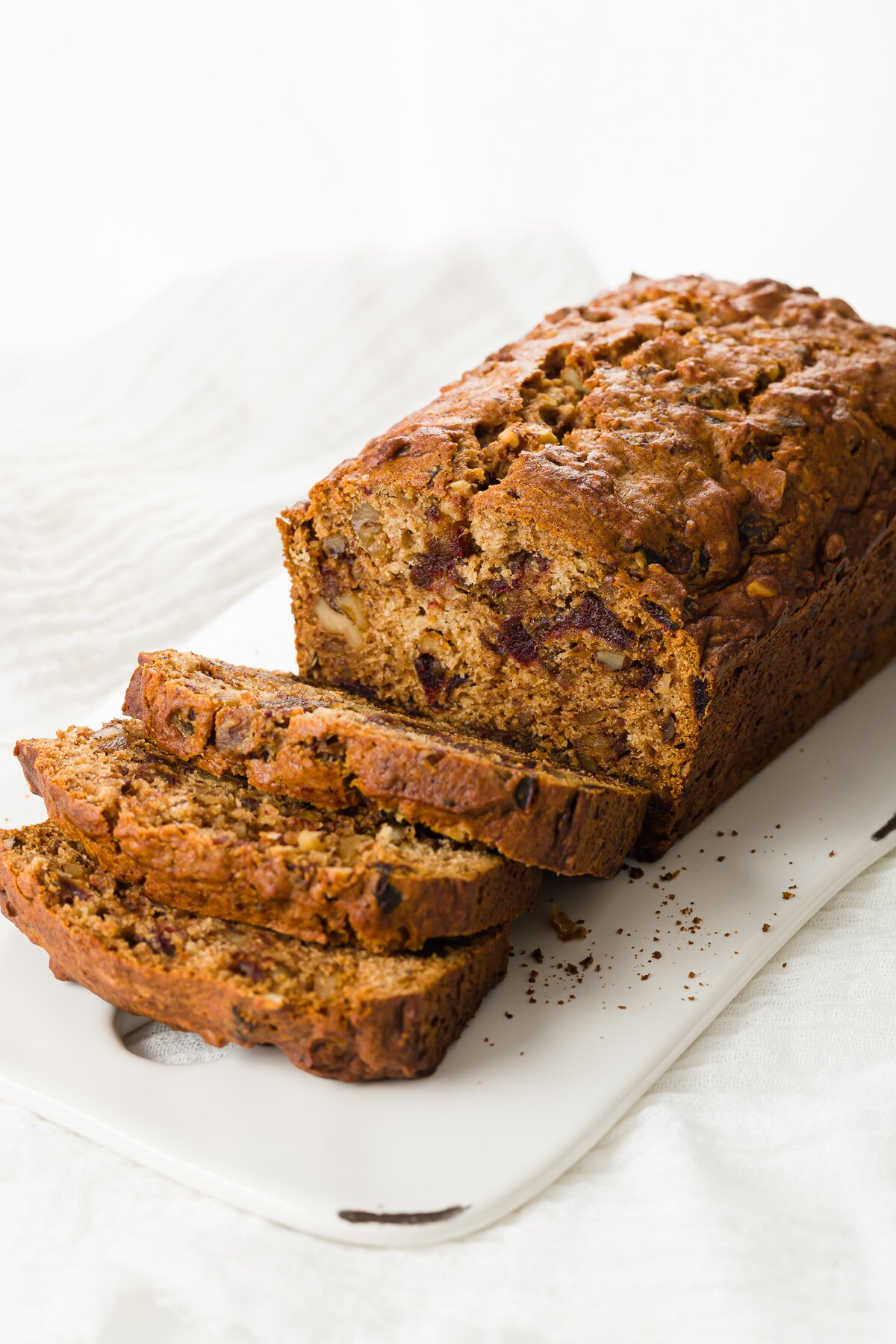 Date nut bread on a white serving plate, partially sliced