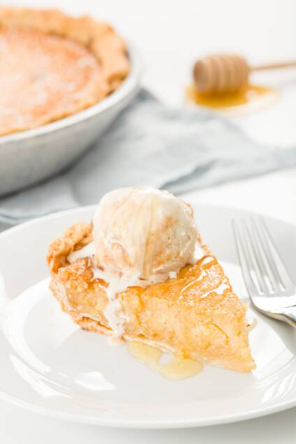 Slice of honey pie on a white plate with a scoop of ice cream on top and a pie in the background