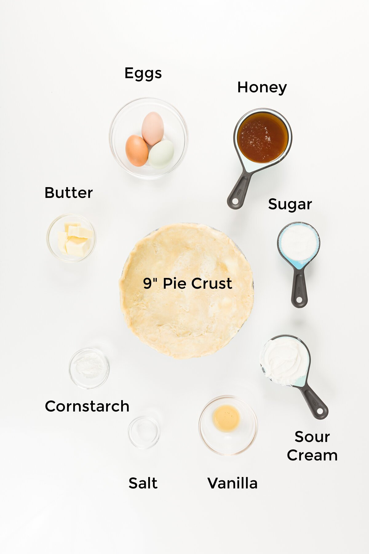 overhead view of ingredients in this honey pie recipe - eggs, honey, sugar, sour cream, vanilla extract, salt, cornstarch, butter, and a 9-inch pie crust