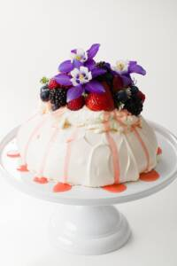 pavlova covered with whipped cream, fresh fruit, and flowers