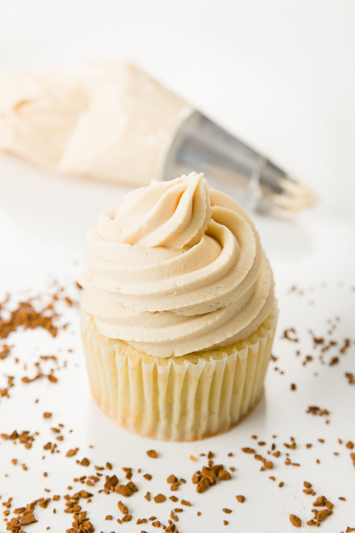 cupcake topped with coffee frosting and a piping bag in the background