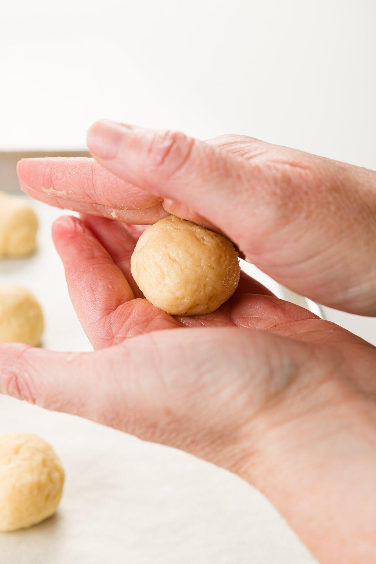 Rolling cookie dough ball between two hands