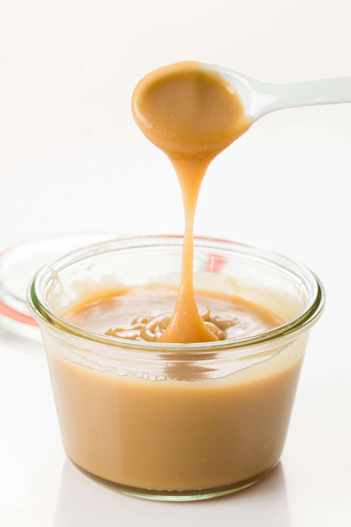Butterscotch sauce dripping from a spoon into a jar