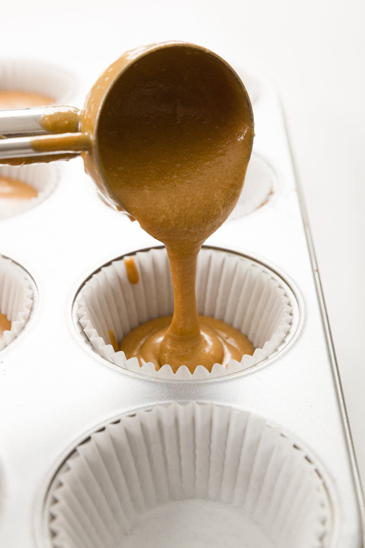 Filling cupcake liner with an ice cream scoop