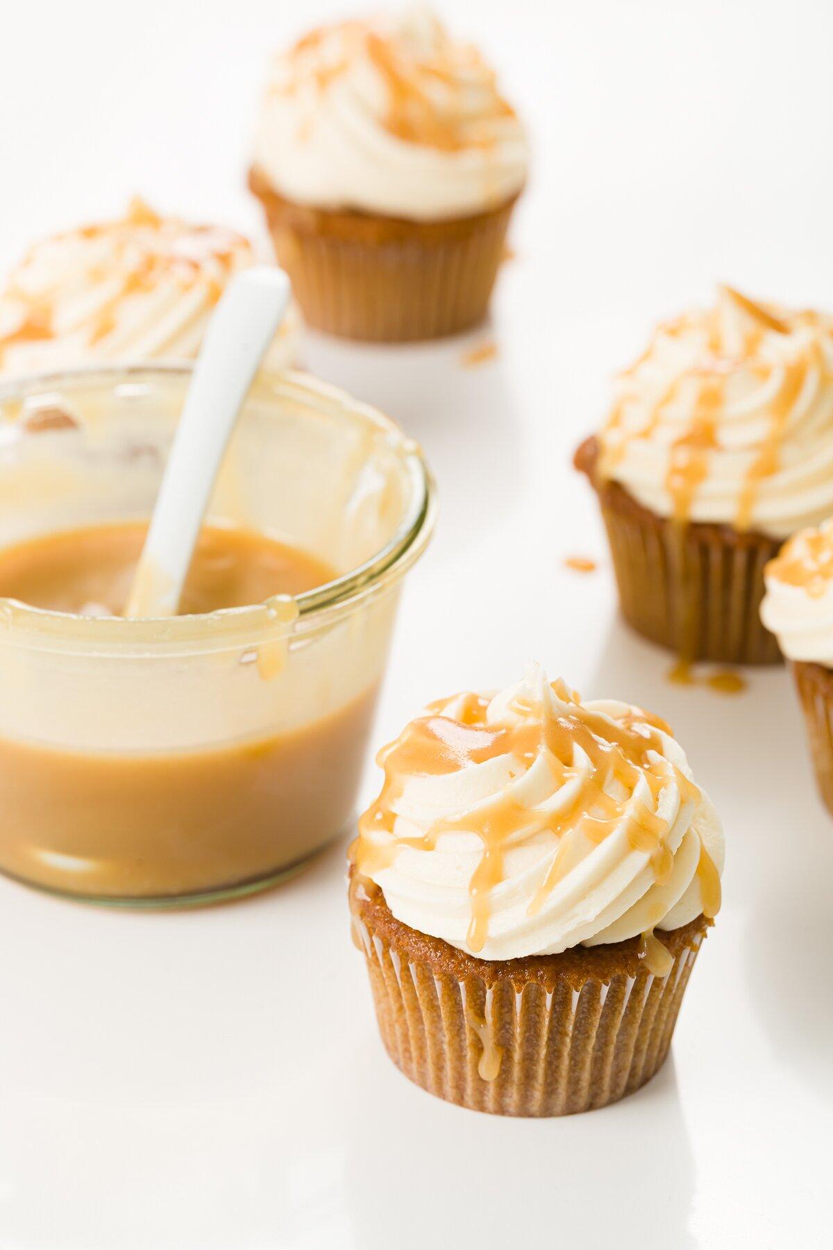 Butterscotch cupcakes with a jar of butterscotch sauce