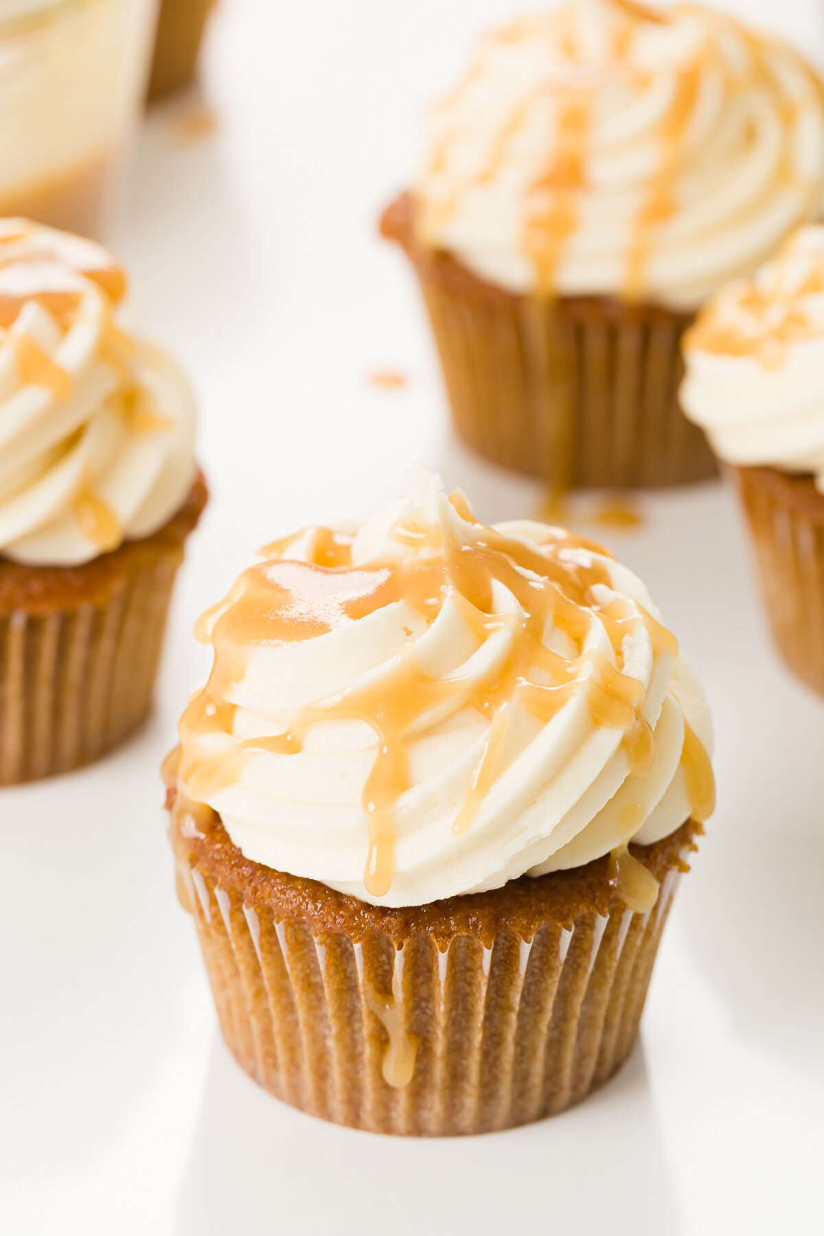A group of butterscotch cupcakes with one in the front