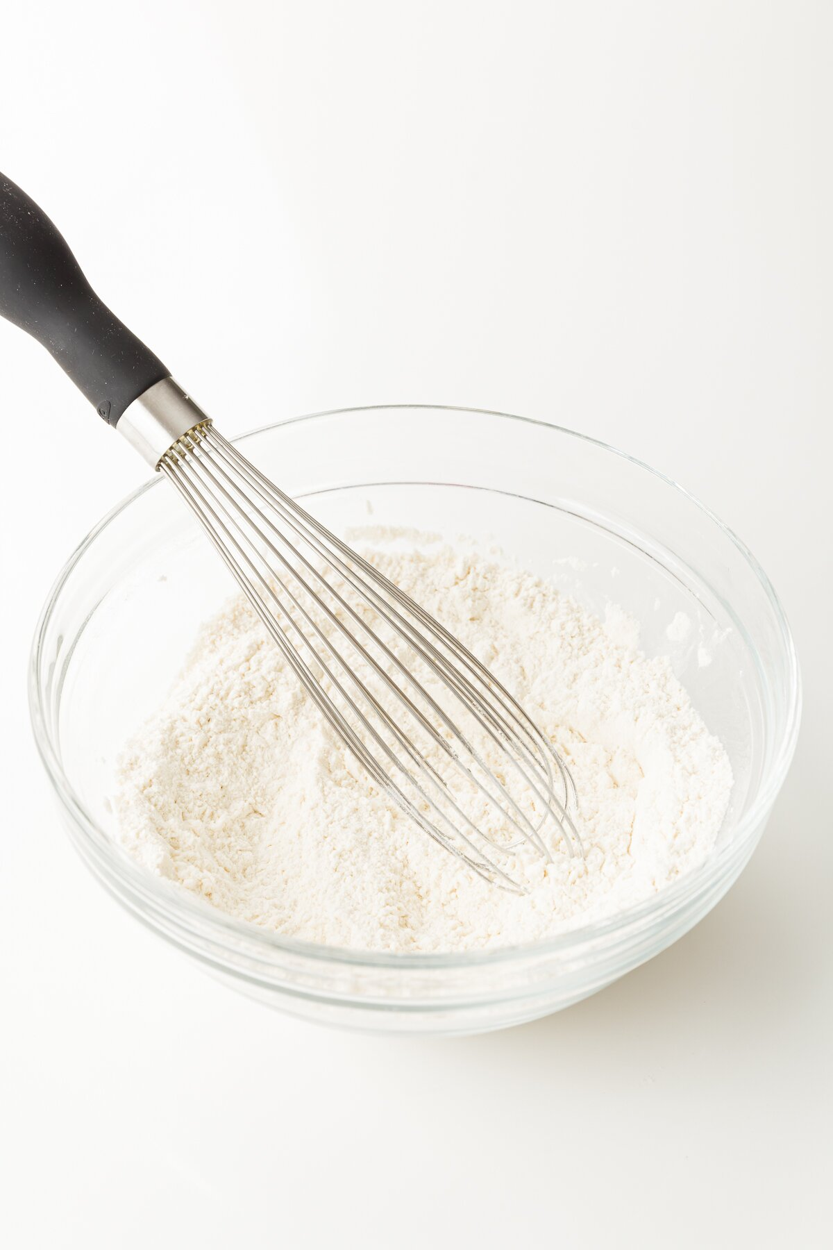 Whisking dry ingredients in a glass bowl.