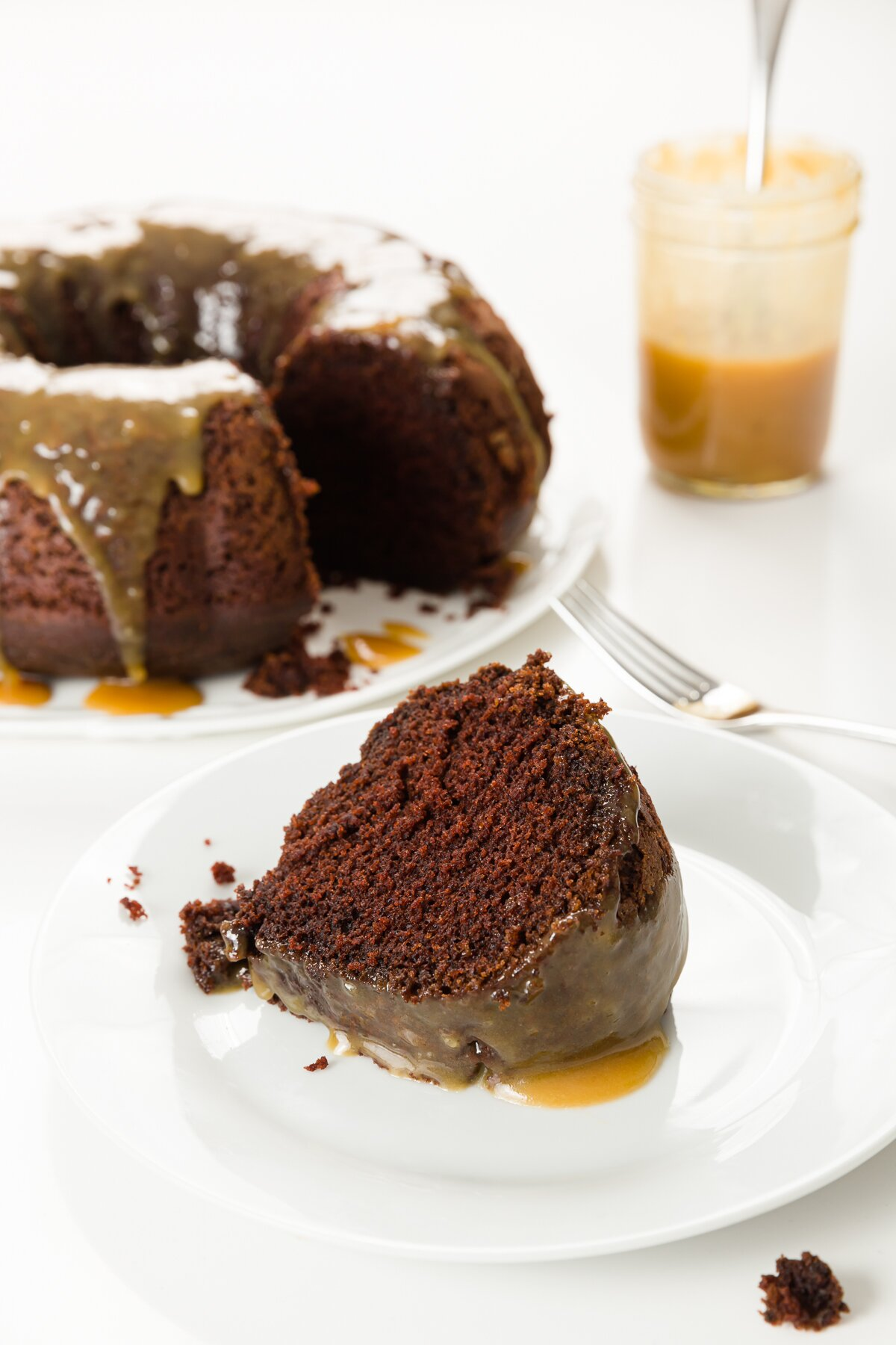 Slice of chocolate whiskey cake with Bundt cake and jar of whiskey sauce in the background