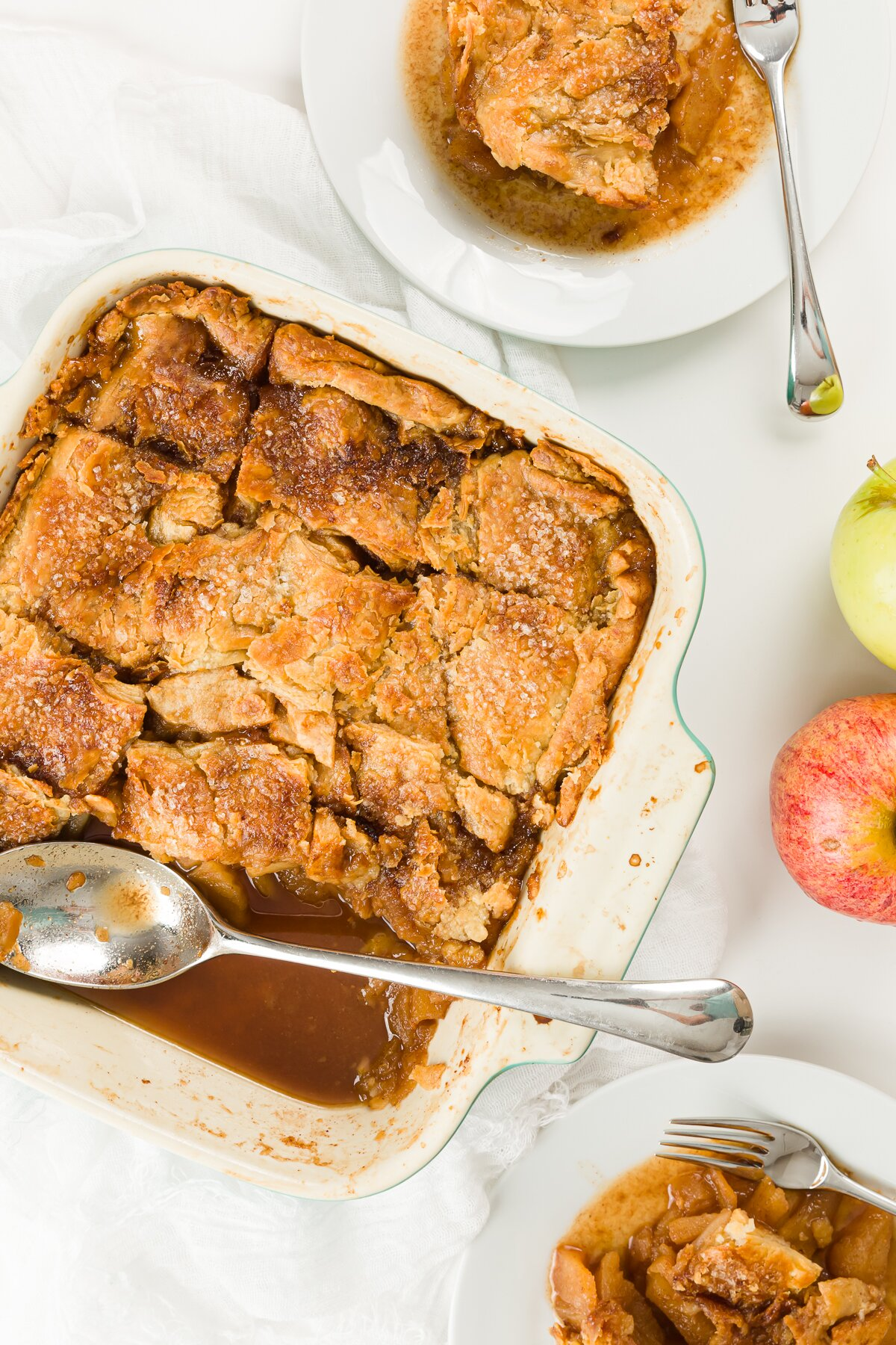 Overhead shot of pan of apple pandowdy, plates with food, and apples