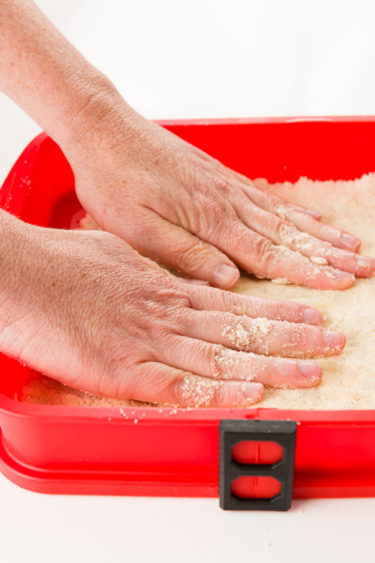 Pressing crust into a red baking pan