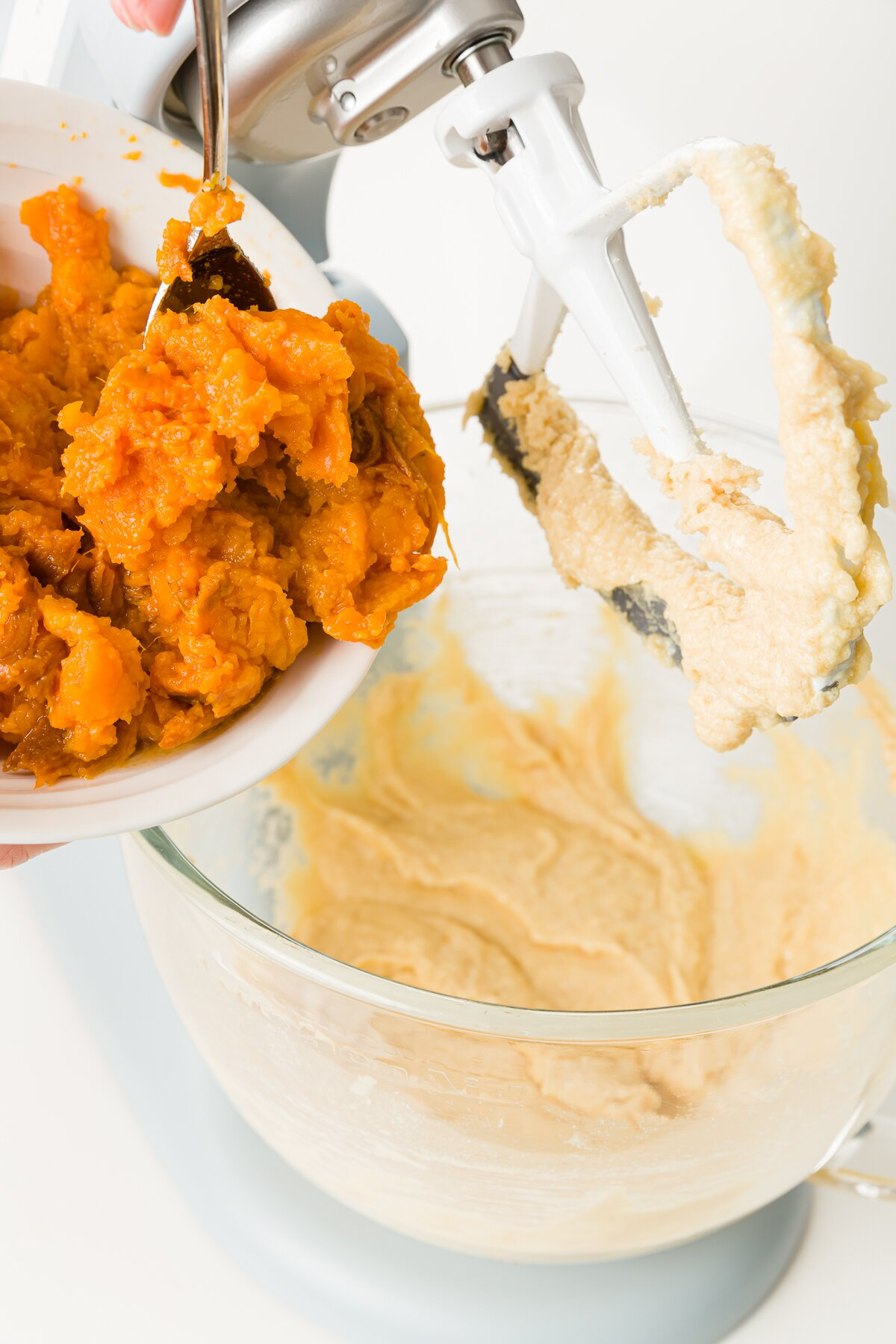 Adding mashed sweet potatoes to a KitchenAid mixer with a blade raised