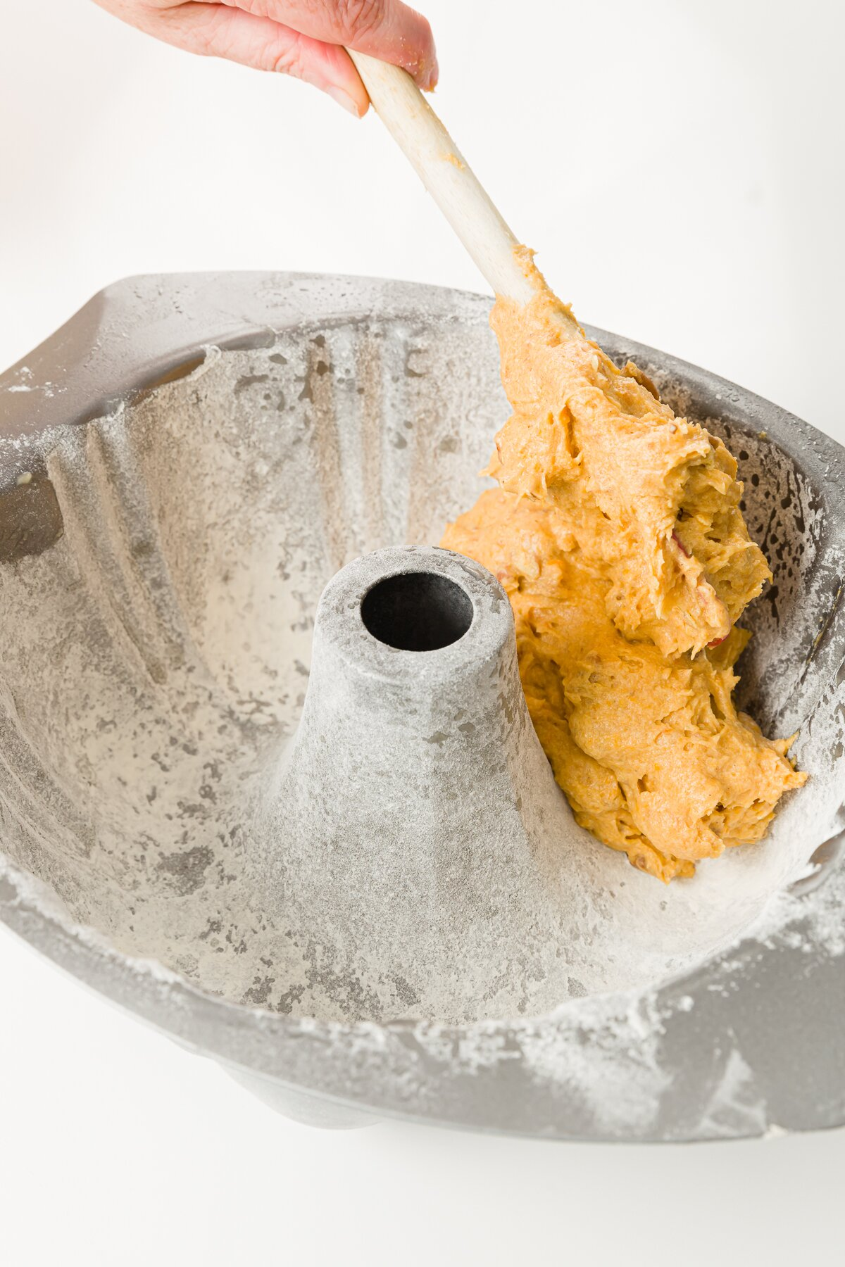 Filling a greased and floured Bundt pan with batter