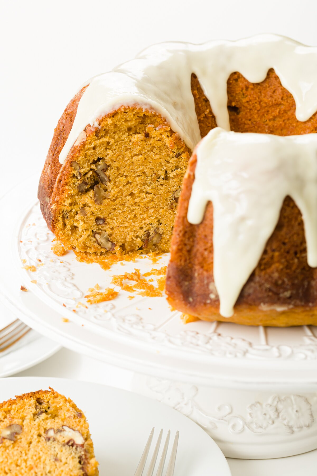 Sweet potato Bundt cake on cake stand with a slice on a plate in front of it