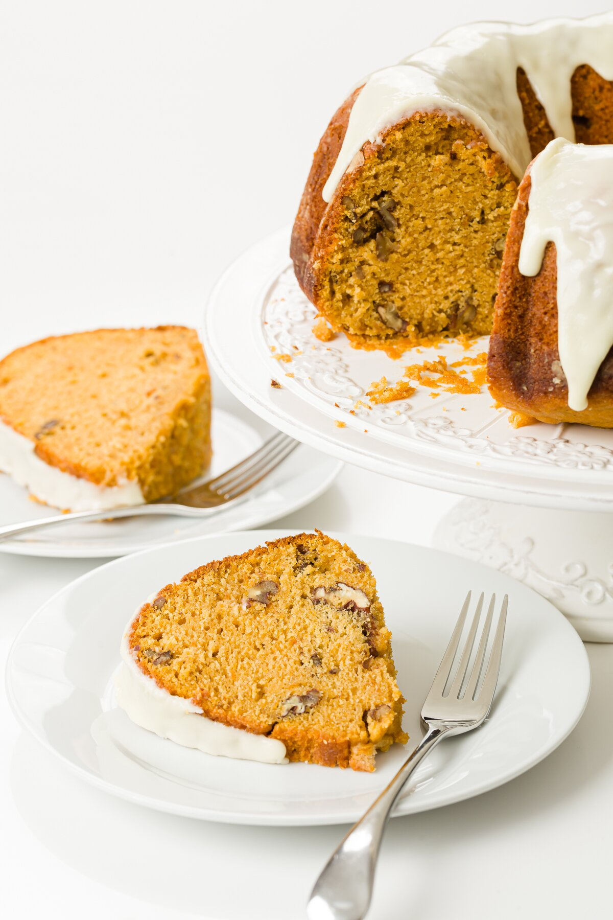 Glazed sweet potato cake on a cake stand with several pieces on white plates in front of it